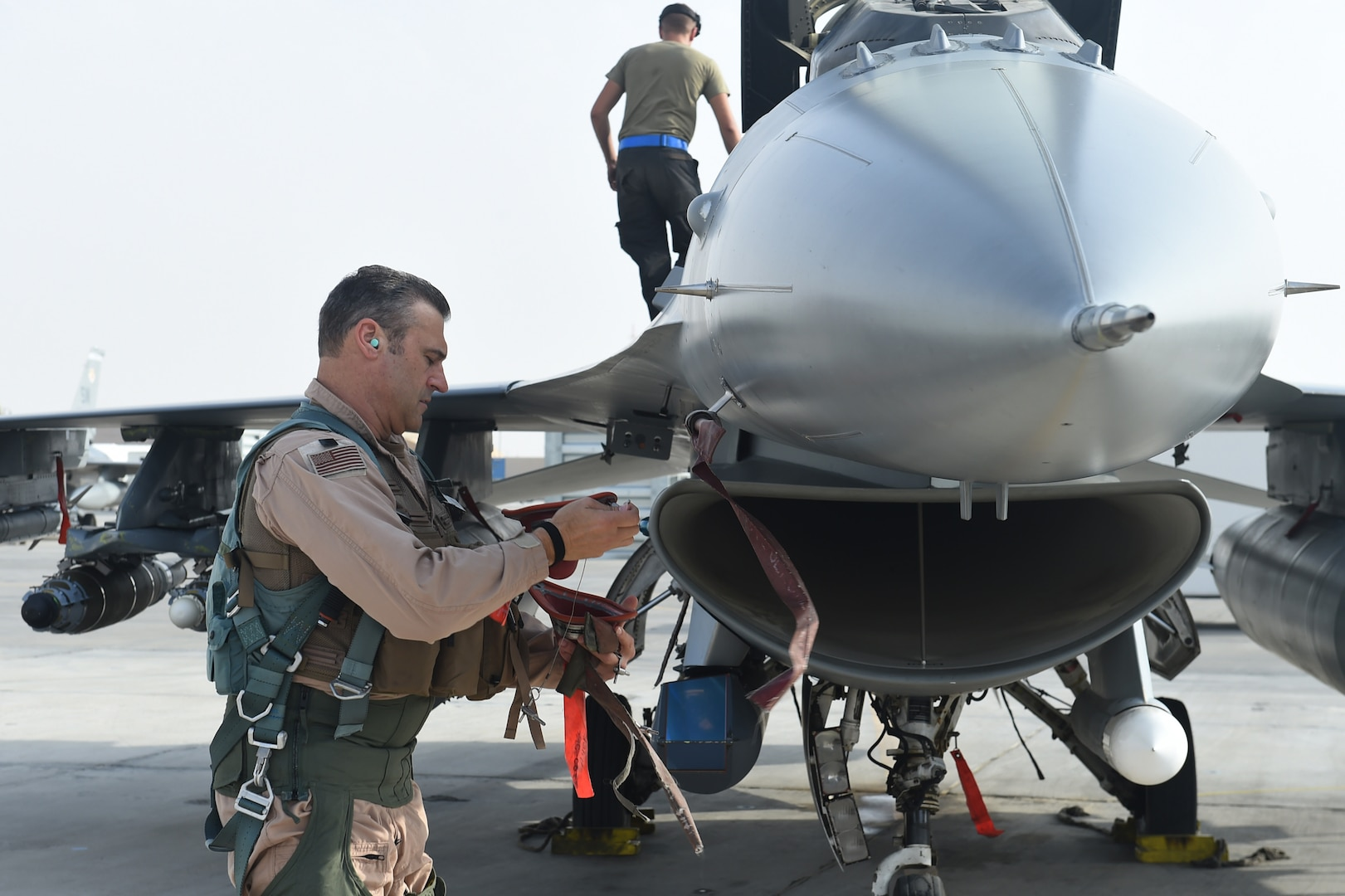 A pilot and crew chief prepare an F-16 Fighting Falcon for take off.