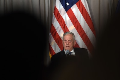 Defense Secretary James N. Mattis speaks with a U.S. flag as his backdrop.