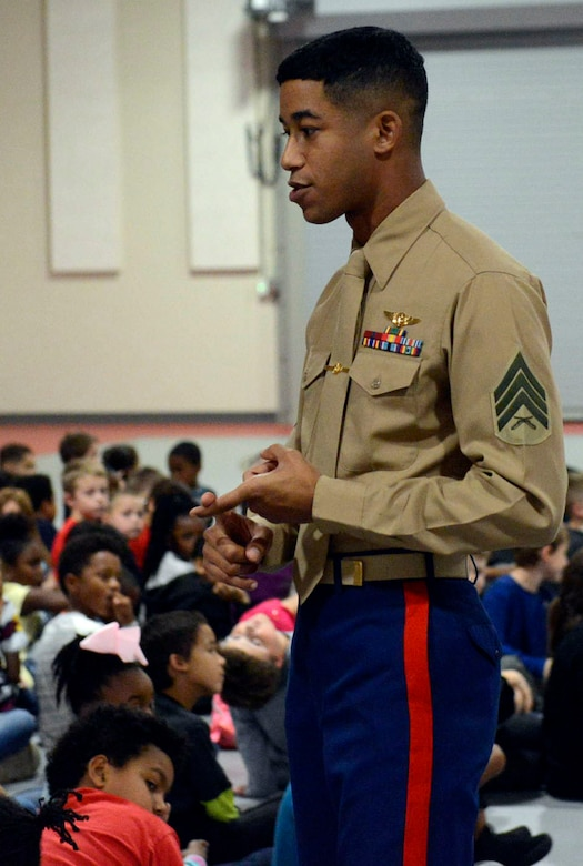 A young black male in Marine Corps tan shirt and blue pants stands in the middle of a group of children as he talks to them.