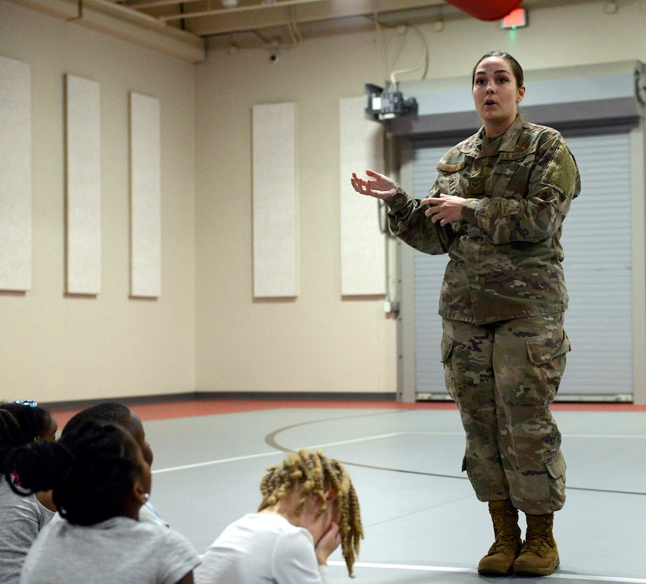 A female in camouflage talks to students in a gym.