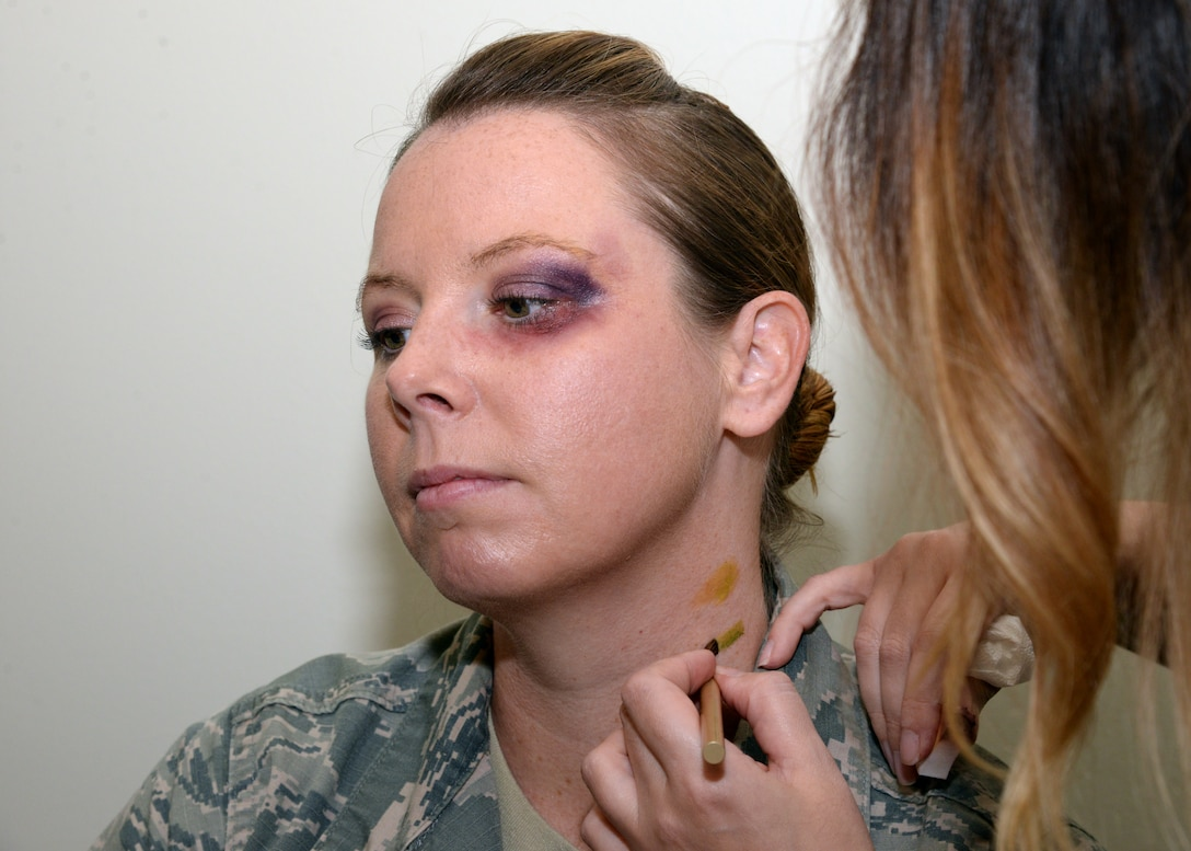 "Master Sgt. Navon Martin, Mental Health Clinic flight chief receives a faux black eye and neck trauma on Oct. 26 during the Black Eye Campaign at Wilford Hall Ambulatory Surgical Center on Joint Base San Antonio-Lackland, Texas. During the campaign, volunteers simulated a black eye or other sign of trauma to see who would ask them about their ""injury"" in an effort to raise awareness of domestic violence."
