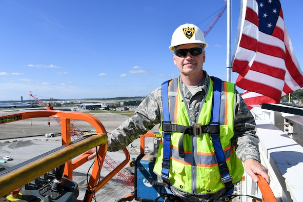 Col. Douglas Strawbridge, commander of the 911th Aiflift Wing, is lifted up to the top of the 911th Airlift Wing's new C-17 hangar at the Pittsburgh International Airport Air Reserve Station, Pa., Oct. 10, 2017. Strawbridge was signing the final roof beam used for the project, a hangar which will house two C-17 aircraft. (U.S. Air Force photo by Senior Airman Beth Kobily)