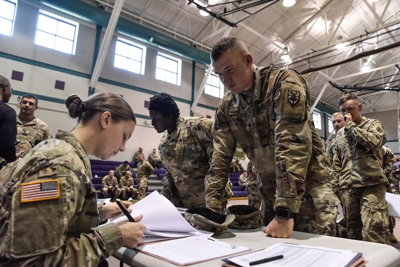 U.S. Army Sgt. Hannah O'Henry and Sgt. Joshua Garcia, 331st Transportation Company, 11th Transportation Battalion, 7th Transportation Brigade (Expeditionary), review Garcia's deployment paperwork to confirm his readiness at Joint Base Langley-Eustis, Virginia, Oct. 22, 2018.