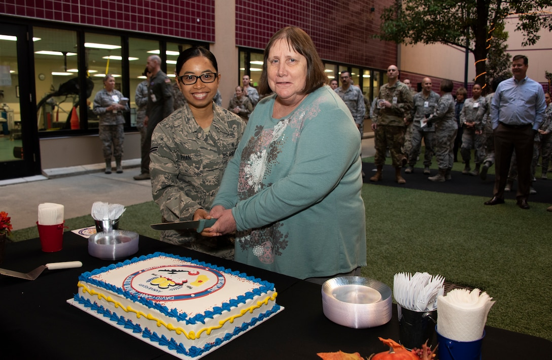 U.S. Air Force Airman 1st Class Phai Phan, 60th Medical Support Squadron and Kathy Wright prepare to cut a special occasion cake, Oct. 30, 2018, Travis Air Force Base, Calif. David Grant U.S. Air Force Medical Center celebrated its 30th Anniversary with cake and testimonials from past and present patients. DGMC is the Air Force's flagship treatment facility, in the United States, providing a full spectrum of health care and patient-centered treatment to a prime service area throughout eight western states. Wright retired Oct. 29, 2018 after 32 years of civil service.(U.S. Air Force Photo by Heide Couch)
