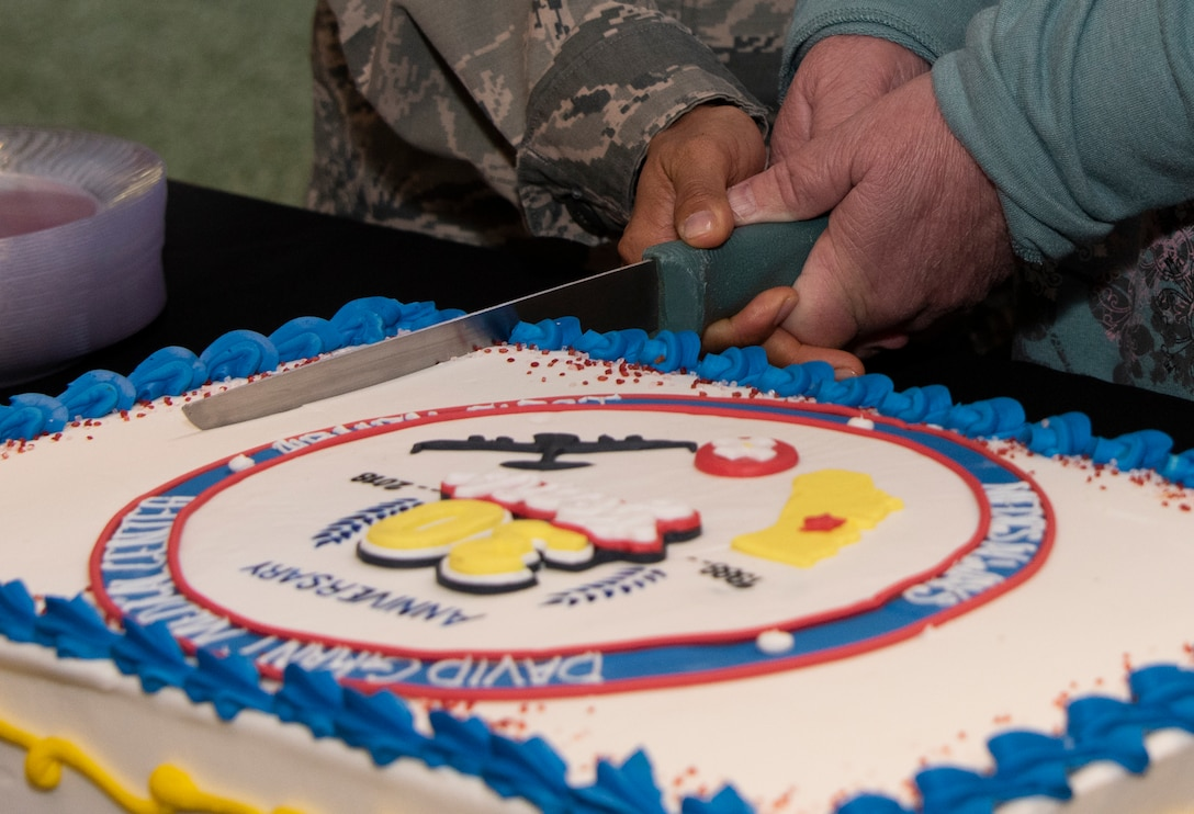 U.S. Air Force Airman 1st Class Phai Phan, 60th Medical Support Squadron and Kathy Wright cut a special occasion cake, Oct. 30, 2018, Travis Air Force Base, Calif. David Grant U.S. Air Force Medical Center celebrated its 30th Anniversary with cake and testimonials from past and present patients. DGMC is the Air Force's flagship treatment facility, in the United States, providing a full spectrum of health care and patient-centered treatment to a prime service area throughout eight western states. Wright retired Oct. 29, 2018 after 32 years of civil service. (U.S. Air Force Photo by Heide Couch)