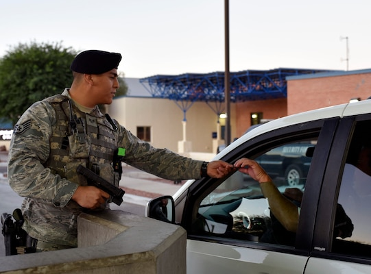 """Air Force Staff Sgt. Rodrigo Acosta, a security forces specialist with the Arizona Air National Guard's 162nd Wing, conducts an identification check at Tucson Air National Guard Base in Tucson, Arizona, Sept. 8, 2018. When not wearing an Air Force uniform as a security forces specialist, Acosta serves as a police officer for the Tucson Police Department. """"Both jobs have the same mindset when it comes to teamwork and building trust among your comrades,"""" he said."""