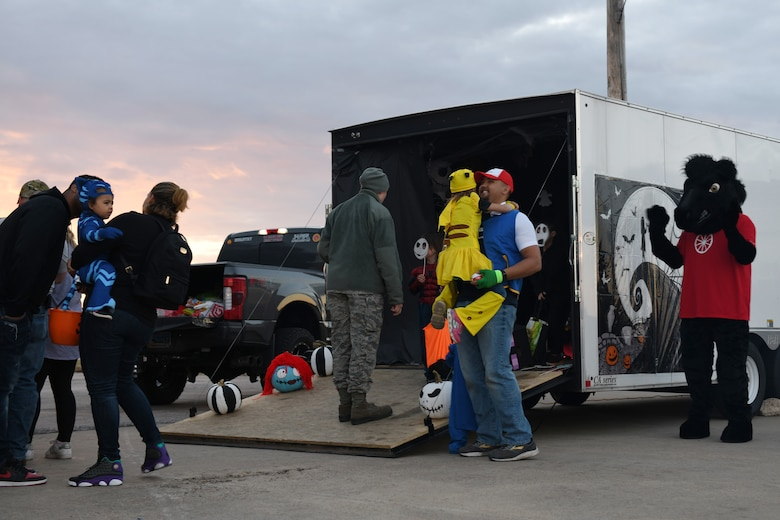 """Children and their families wait in line before entering a """"Nightmare Before Christmas"""" themed trailer provided by the 28th Logistics Readiness Squadron at Ellsworth Air Force Base, S.D., Oct. 26, 2018. Volunteers from the 28th Bomb Wing decorated their personal and work vehicles with Halloween themes and put them on display. (U.S. Air Force photo by Airman 1st Class Christina Bennett)"""