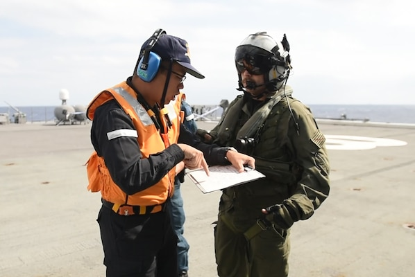 PHILIPPINE SEA (Oct. 31, 2018) Naval Aircrewman (Helicopter) 2nd Class Ryan Quinn, assigned to Helicopter Maritime Strike Squadron (HSM) 77, and a member of the Japan Maritime Self-Defense Force ship JS Huyuga (DDH-181) discuss an Acquisition and Cross Servicing Agreement Logistics Exchange during Keen Sword 19. Keen Sword 19 is a joint, bilateral field-training exercise involving U.S. military and Japan Maritime Self-Defense Force personnel, designed to increase combat readiness and interoperability of the Japan-U.S. alliance.
