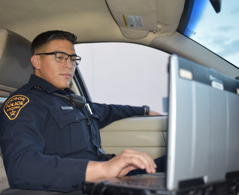 "Air Force Staff Sgt. Rodrigo Acosta, a security forces specialist with the Arizona Air National Guard's 162nd Wing and a Tucson Police Department police officer, reviews data on his patrol car laptop in Tucson, Arizona, Aug. 28, 2018. Acosta said he thrives in settings outside of the office environment. ""I can't see myself sitting behind a desk at all. I think I would fall asleep,"" he said. ""Law enforcement and security forces always keeps me on my toes."""