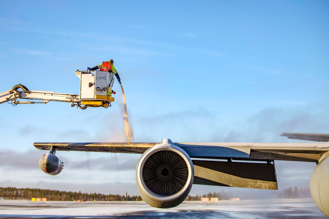 A worker in a raised container sprays an aircraft wing to de-ice it.