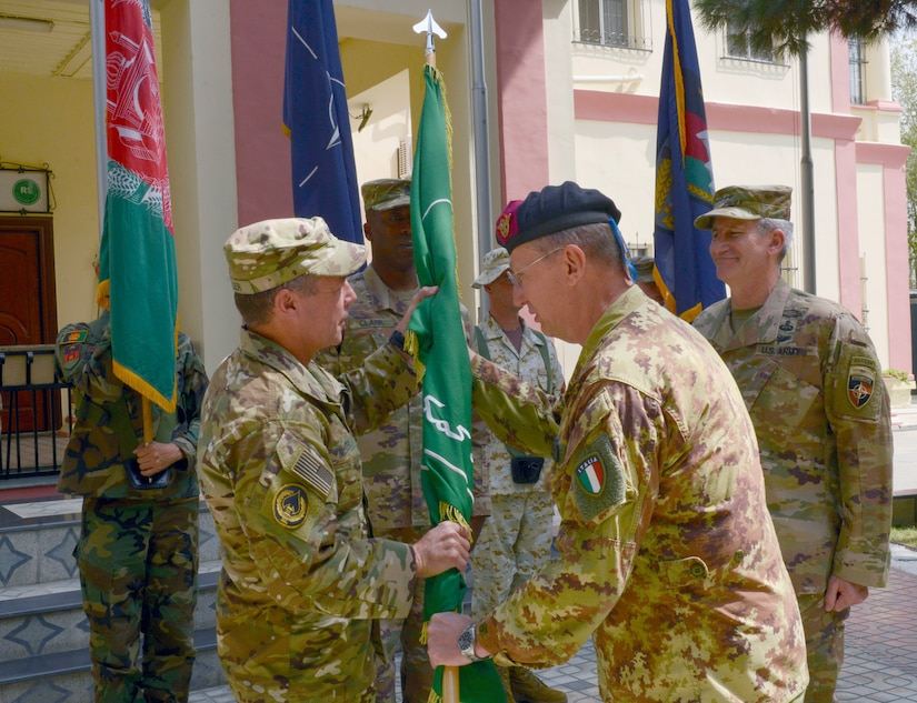 An Italian Army general passes the Resolute Support Mission flag to U.S. Army Gen. Austin S. Miller.