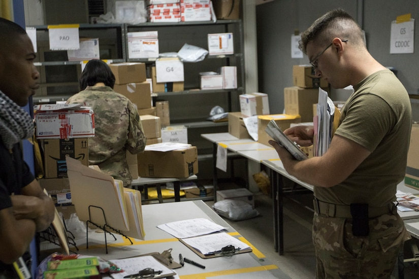 U.S. Army Spc. James Day, a human resources specialist with the 151st Regional Support Group, Massachusetts Army National Guard, attached to U.S. Army Central, searches through a stack of letters for anything belonging to a visitor to the USARCENT mail room at Camp Arifjan, Kuwait, Aug. 20, 2018. Providing convenient mail service to deployed Soldiers promotes morale and cohesion within units.