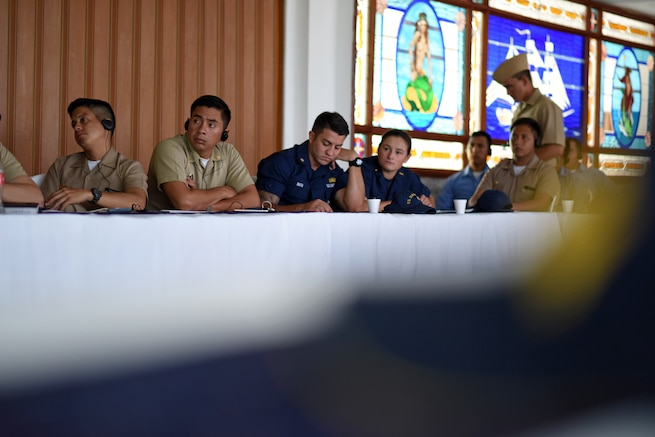 Military officials listen to a briefing