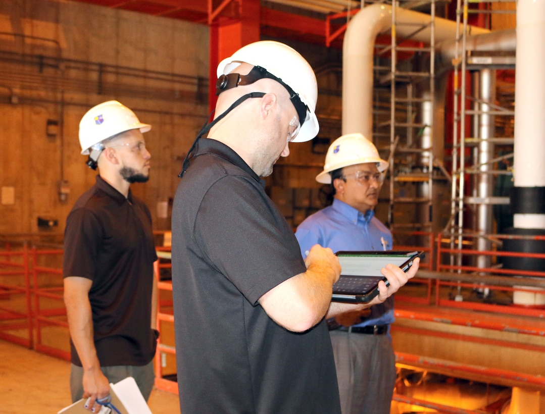 A representative with NORESCO, a Super Energy Savings Performance contractor, walks through one of the facilities at Arnold Air Force Base to look at lighting and other areas where energy savings might occur. NORESCO recently received a $19.7 million energy savings performance contract award to perform work at Arnold through the Air Force Civil Engineering Center and Defense Logistics Agency. Pictured in back is Reggie Floyd, Energy and Utility Program Manager, and Kazi Mamun, Arnold Resource Efficiency Manager. (U.S. Air Force photo by Deidre Ortiz)