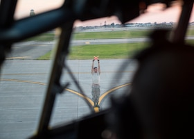 U.S. Air Force Airman 1st Class Ryan Dunlap, a crew chief with the 133rd Aircraft Maintenance Squadron, marshals a C-130 Hercules into the proper parking spot during a training in St. Paul, Minn., Aug. 8, 2018.