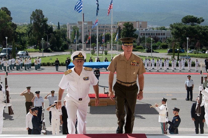 Marine Corps Gen. Joe Dunford, chairman of the Joint Chiefs of Staff, walks up stairs with a sailor.