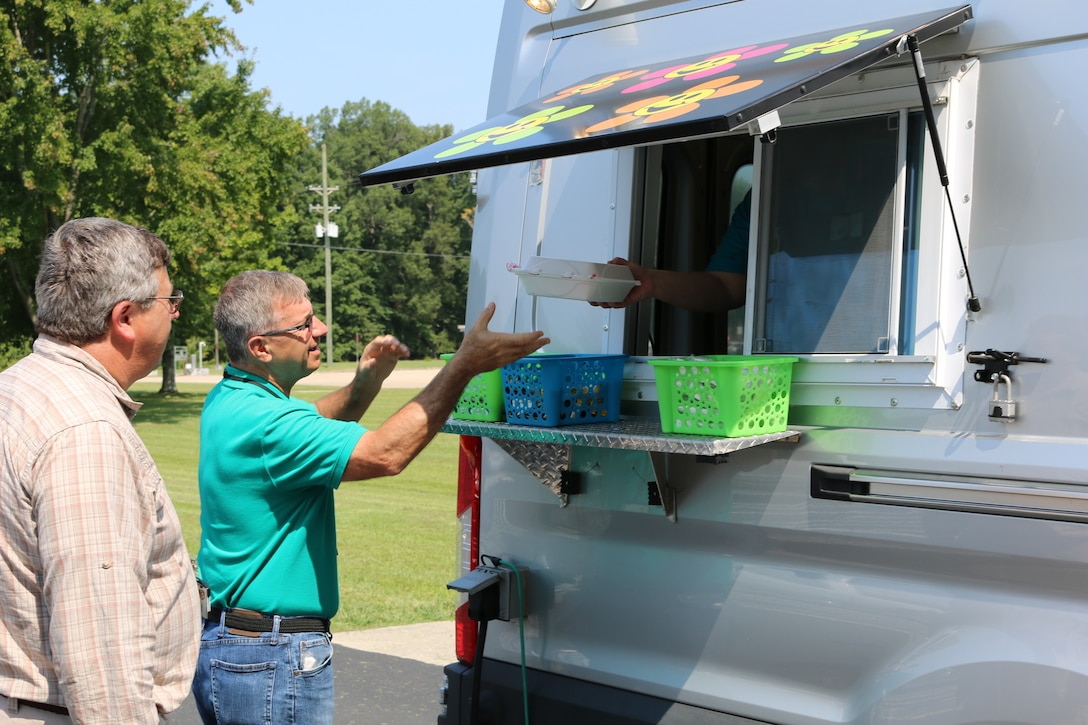Gene Klingensmith, center, picks up his order from the Crazy Daisies food truck. Klingensmith was among those who visited the food truck during its first day of operations at Arnold Air Force Base. (U.S. Air Force photo by Bradley Hicks)