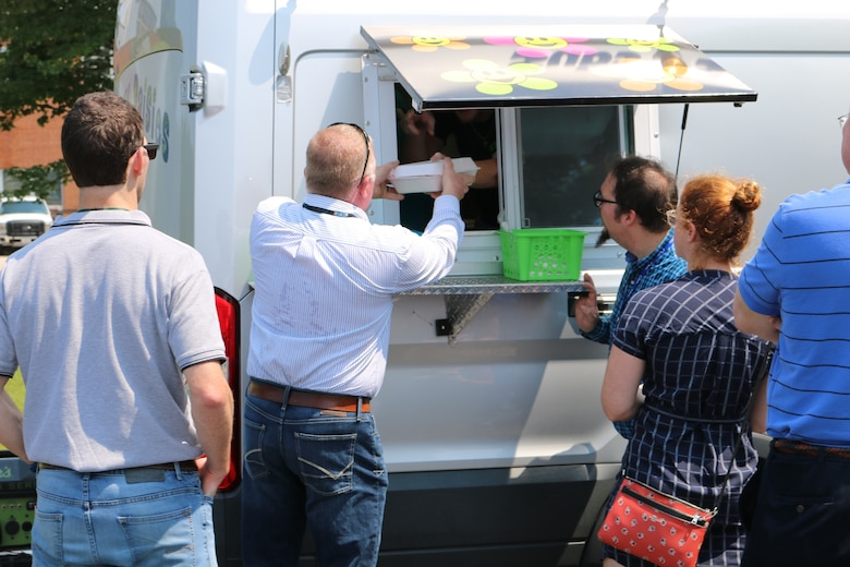 An AEDC team member receives his order from the Crazy Daisies food truck during its first day of operations at Arnold Air Force Base. The food truck, which is located in the parking lot of the Main Auditorium, began business at Arnold on Aug. 14. (U.S. Air Force photo by Bradley Hicks)