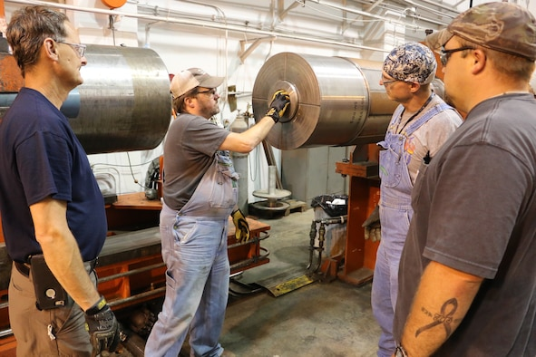 Outside machinists Tim Gilliam, left, and Will Jacques, right, and boilermaker Troy Caldwell, second from right, look on as Lead Outside Machinist Mark Carson loads a projectile into the launcher. The craftsmen are helping to improve weather encounter testing at the range. (U.S. Air Force photo by Bradley Hicks)