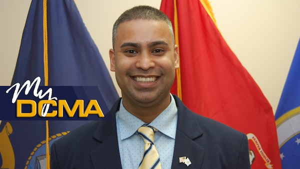 A smiling man in a suit stands in front of the various DCMA flags.