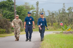 Staff Sgt. William Muira, from the Hawaii National Guard's CBRNE Enhanced Response Force Package (CERFP) Team, escorts FEMA Urban Search and Rescue members from California Task Force 3 while they perform a wide-area assessment in the wake of Hurricane Lane in Kea'au, Hawaii, on Aug. 27, 2018.