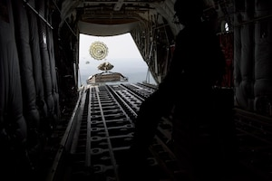 A long shot from the inside of a C-130J aircraft shows a parachuted pallet simulating heavy equipment sliding out the open back of the plane.