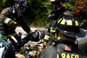 Firefighters in MOPP gear practice rescuing an Airman in MOPP gear from a car crash.