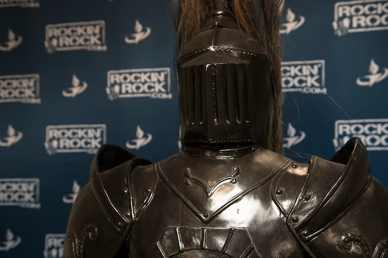 A suit of armor is posed in front of a backdrop.