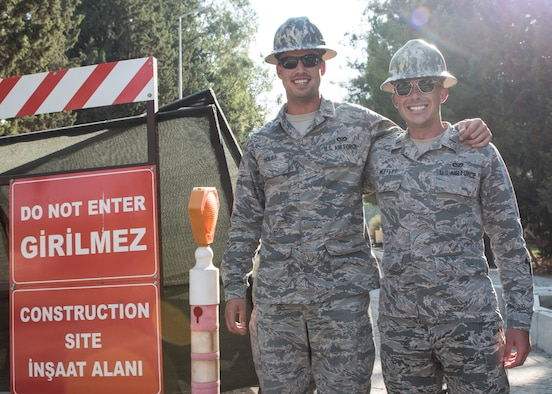 U.S. Air Force 2nd Lt. Alexander Holba; 39th Civil Engineer Squadron construction management chief; and U.S. Air Force 1st Lt. Timothy Moffett; 39th CES installation manager flight commander; pose for a photo outside of a construction zone at Incirlik Air Base; Turkey; Sept. 4; 2018.