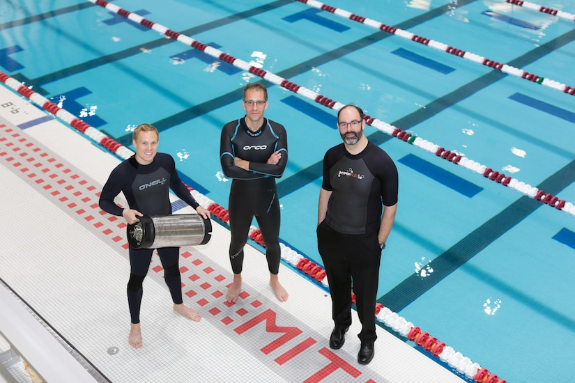 From left, graduate student Anton Cottrill, Dr. Jacopo Buongiorno and Dr. Michael Strano try out their neoprene wetsuits at a pool at MIT's athletic center, June 15, 2018. Cottrill is holding the pressure tank used to treat the wetsuits with heavy inert gasses. Courtesy photo by Susan Young