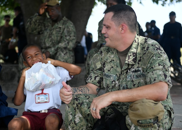 A U.S. Navy Sailor  helps a student at Gimnasio Cristiano de Bocachica children's school open his lunch bag.