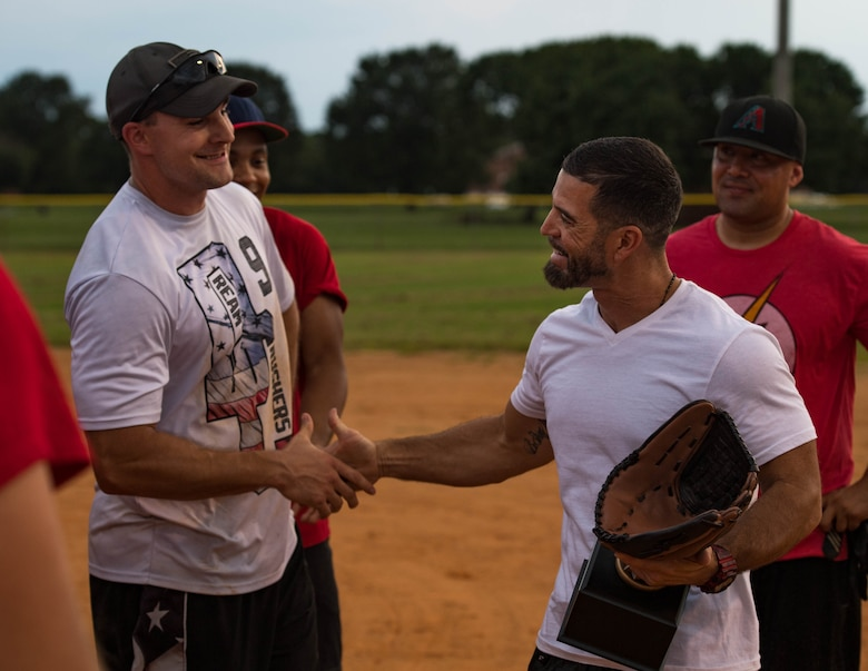 Tony Arroyo, 633rd Force Support Squadron fitness center director, hands the trophy to the 30th Intelligence Squadron softball team during the intramural softball championship at Joint Base Langley-Eustis, Virginia, Aug. 30, 2018.