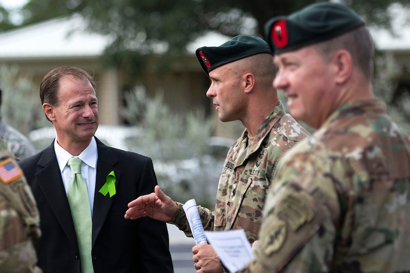 A man speaks with two soldiers.