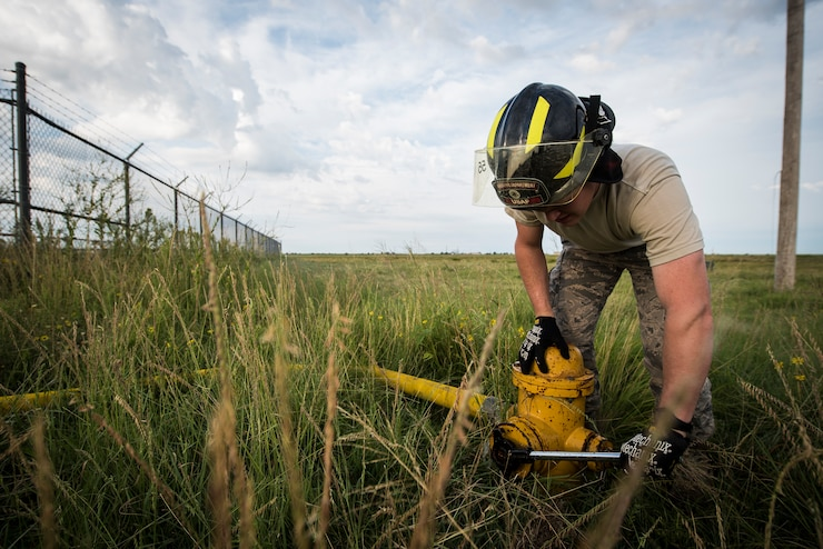 An Airman tightens the bolts on a fire hydrant in a grassy field