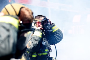 Two men wearing fire protective equipment put on their fire protective masks with smoke all around them.