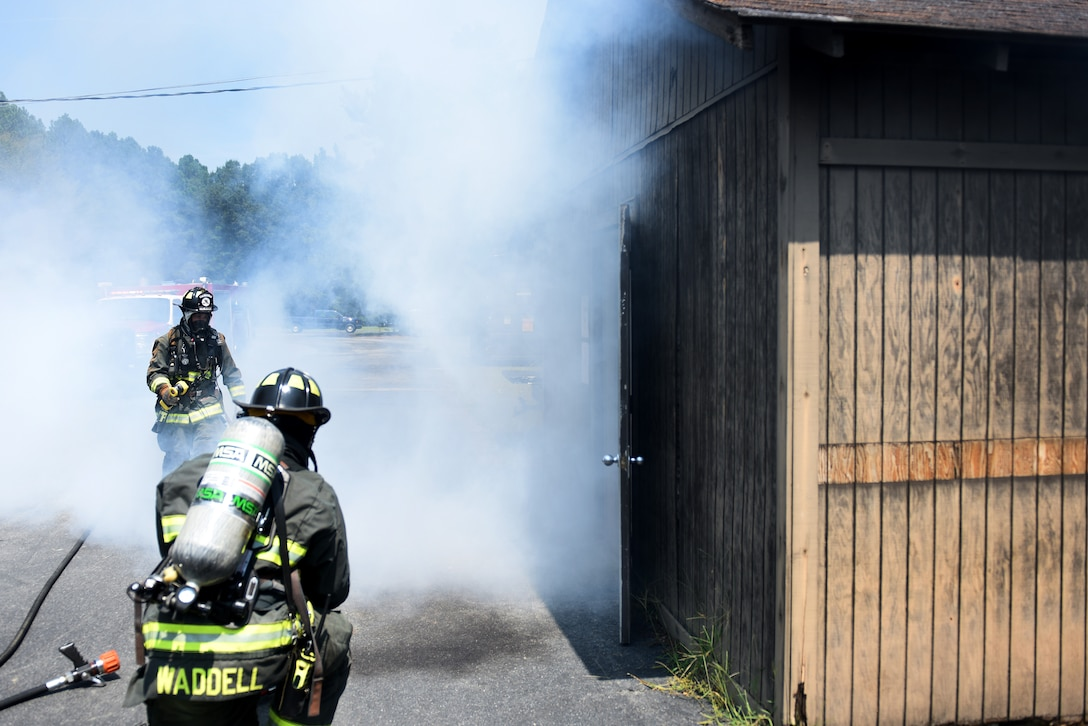 Two men wearing fire protective equipment walk towards a wood cabin with smoke coming out of the front door.