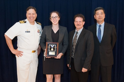 Stephanie Ferrone, a physicist in Carderock's Underwater Electromagnetic Signatures and Technology Division, receives the Vice Adm. Samuel L. Gravely Jr. Award for achievement in equity and diversity at the Naval Surface Warfare Center, Carderock Division Honor Awards ceremony Aug. 28, 2018, in West Bethesda, Md. From left to right: Commanding Officer Capt. Mark Vandroff; Ferrone; Mike Slater, division head of Carderock's Signatures Measurement Technologies and Systems Division; and Paul Shang, Carderock's acting technical director. (U.S. Navy photo by Nicholas Brezzell/Released)