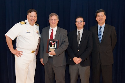Stephen Neely, a naval architect in Carderock's Computational Propulsors Branch, receives the Rear Adm. George W. Melville Award for engineering excellence at the Naval Surface Warfare Center, Carderock Division Honor Awards ceremony Aug. 28, 2018, in West Bethesda, Md. From left to right: Commanding Officer Capt. Mark Vandroff; Scott Black, accepting on Neely™s behalf; Steve Ouimette, deputy head of the Naval Architecture and Engineering Department; and Dr. Paul Shang, acting technical director. (U.S. Navy photo by Nicholas Brezzell/Released)