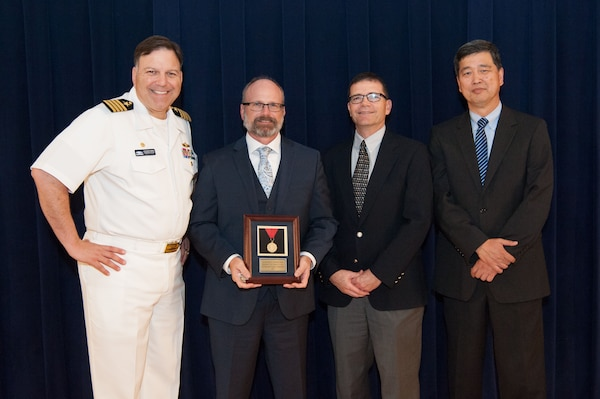 Dr. Timothy Coats, lead for Combatant Craft Division's Unmanned Maritime Mobility Group, receives the Capt. Harold E. Saunders Award for exemplary technical management at the Naval Surface Warfare Center, Carderock Division Honor Awards ceremony Aug. 28, 2018, in West Bethesda, Md. From left to right: Commanding Officer Capt. Mark Vandroff; Coats; Steve Ouimette, deputy head of the Naval Architecture and Engineering Department; and Dr. Paul Shang, acting technical director. (U.S. Navy photo by Nicholas Brezzell/Released)