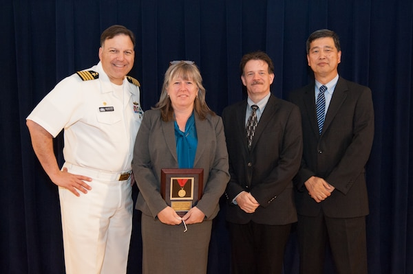 Amy Le Doux, Carderock's customer advocate for the Virginia-class Program Office (PMS450), receives the Capt. Harold E. Saunders Award for exemplary technical management at the Naval Surface Warfare Center, Carderock Division Honor Awards ceremony Aug. 28, 2018, in West Bethesda, Md. From left to right: Commanding Officer Capt. Mark Vandroff; Coats; Mike Slater, division head of Carderock's Signatures Measurement Technologies and Systems Division; and Dr. Paul Shang, acting technical director. (U.S. Navy photo by Nicholas Brezzell/Released)