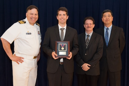 Dr. Brian Glover, a physicist in Carderock's Theory, Modeling and Analysis Branch, receives the Rear Adm. David W. Taylor Award for outstanding scientific achievement at the Naval Surface Warfare Center, Carderock Division Honor Awards ceremony Aug. 28, 2018, in West Bethesda, Md. From left to right: Commanding Officer Capt. Mark Vandroff; Glover; Mike Slater, division head of Carderock's Signatures Measurement Technologies and Systems Division; and Dr. Paul Shang, acting technical director. (U.S. Navy photo by Nicholas Brezzell/Released)
