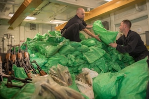 Sailors stack a cache of more than 1,000 AK-47 automatic rifles aboard the guided-missile destroyer USS Jason Dunham (DDG 109).