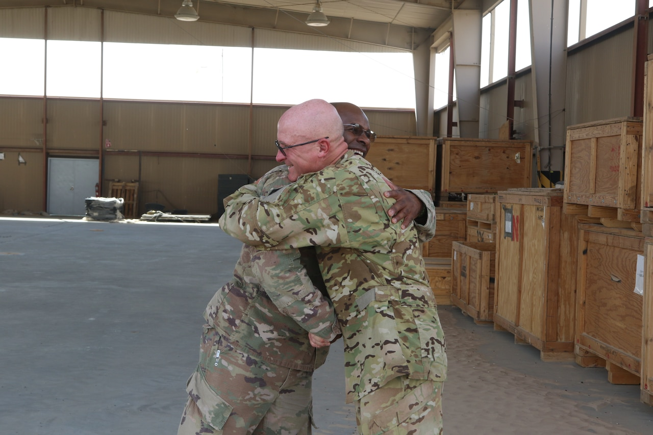 Army Staff Sgt Robert Morneau, right, a crew chief assigned to 1st Battalion, 126th Aviation Regiment (General Support Aviation Battalion), embraces Army Sgt 1st Class Giovanni Ford, the 449th Combat Aviation Brigade Headquarters and Headquarters Company's supply sergeant at Camp Buehring, Kuwait, Aug. 21, 2018. The two noncommissioned officers are childhood comrades that haven't seen each other for 30 years until they ran into each other on their 2017-2018 deployment in support of Operations Inherent Resolve and Spartan Shield. Army photo by Capt. Briana McFarland
