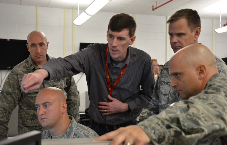 Keith Ewasiuk, (center) maintenance operations control center manager for the Air Force Technical Applications Center, explains to Col. Ralph E. Bordner III (lower right), AFTAC vice commander, how data is analyzed after the nuclear treaty monitoring center transfers the mission from its primary location at Patrick AFB, Fla., to its alternate location in Millington, Tenn.  Also pictured (l to r):  Maj. William J. Pattinson, 22nd Surveillance Squadron director of operations; Staff Sgt. Beau Brennan, subsurface analyst; and Lt. Col. Joseph H. Shupert, 709th Surveillance and Analysis Group deputy commander. (U.S. Air Force photo by Susan A. Romano)