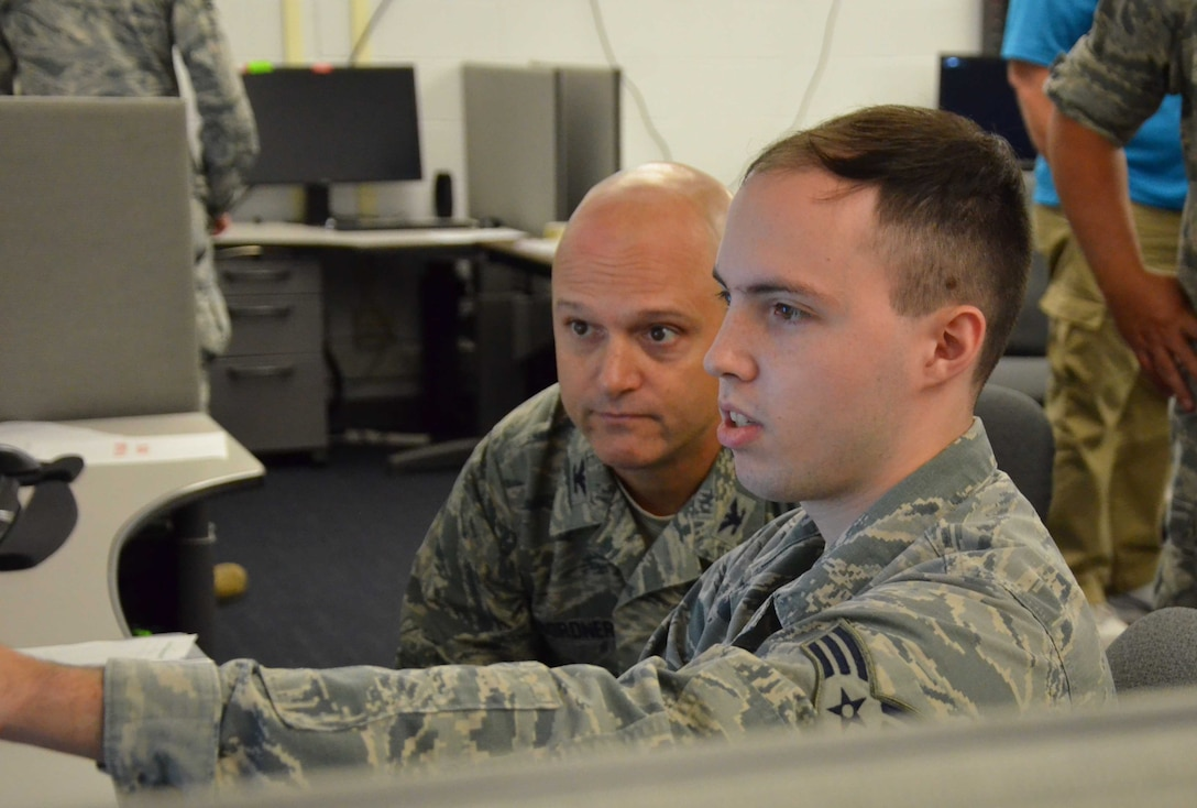 Senior Airman Joseph Stanley (right), a subsurface operations manager at the Air Force Technical Applications Center, describes to Col. Ralph E. Bordner III, AFTAC vice commander, how seismic signals and waveforms appear after the nuclear treaty monitoring mission is transferred from the center's primary location at Patrick AFB, Fla., to its alternate location in Millington, Tenn.  AFTAC recently exercised its ability to relocate in the event of a natural or man-made disaster.  (U.S. Air Force photo by Susan A. Romano)