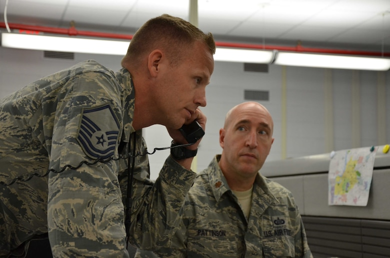 Master Sgt. Michael Nolan, cyber operations superintendent, fields a phone call from his headquarters at Patrick AFB, Fla., during a Contingency of Operations exercise Aug. 14-15, 2018, as Maj. William J. Pattinson looks on.  Nolan was one of several members of the Air Force Technical Applications Center who participated in the exercise to test the nuclear treaty monitoring center's ability to transfer the mission from its primary location to its alternate site in Millington, Tenn.  (U.S. Air Force photo by Susan A. Romano)
