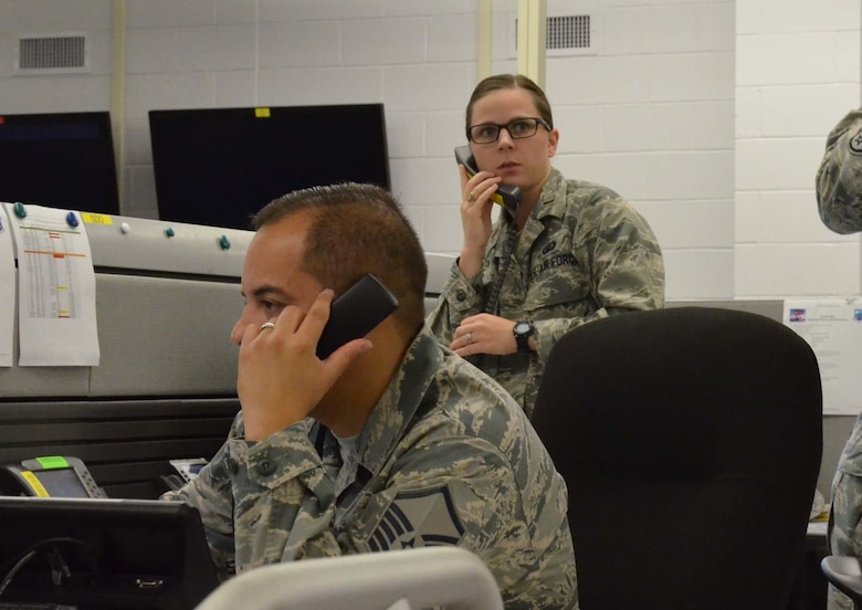2nd Lt. Morgan Snyder, senior duty officer at the Air Force Technical Applications Center headquartered at Patrick AFB, Fla., takes a call during a Contingency of Operations exercise that tested the nuclear treaty monitoring center's ability to transfer its vital mission from Patrick to its alternate location in Millington, Tenn., as Master Sgt. Jorge Garcia, AFTAC operations manager, relays information to his counterparts in Florida.  (U.S. Air Force photo by Susan A. Romano)