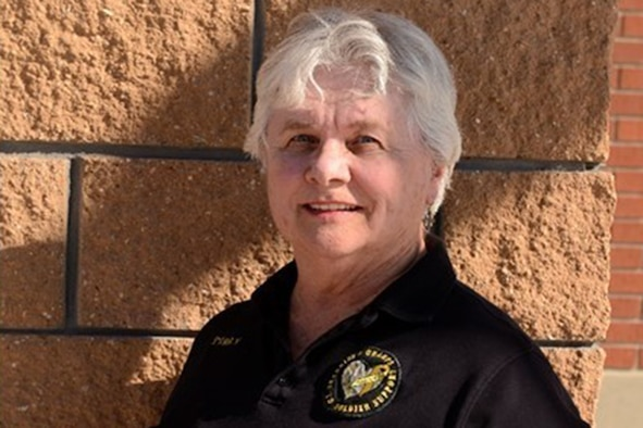 A woman poses against a brick wall while wearing a black polo shirt.