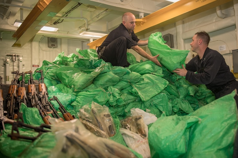GULF OF ADEN (Aug. 30, 2018) Sailors stack a cache of more than 1,000 AK-47 automatic rifles aboard the guided-missile destroyer USS Jason Dunham (DDG 109). The ship's visit, board, search and seizure team seized the weapons from a skiff during a flag verification boarding as part of maritime security operations. Dunham is deployed to the U.S. 5th Fleet area of operations in support of naval operations to ensure maritime stability and security in the Central Region, connecting the Mediterranean and the Pacific through the western Indian Ocean and three strategic choke points. (Photo by Mass Communication Specialist 3rd Class Jonathan Clay)