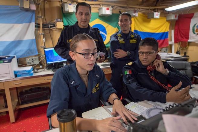 U.S. and multinational Sailors work at desks on USS Gunston Hall.
